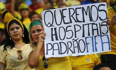Uma manifestante segura cartaz durante partida do Brasil contra o México pelo grupo A da Copa das Confederações, em Fortaleza